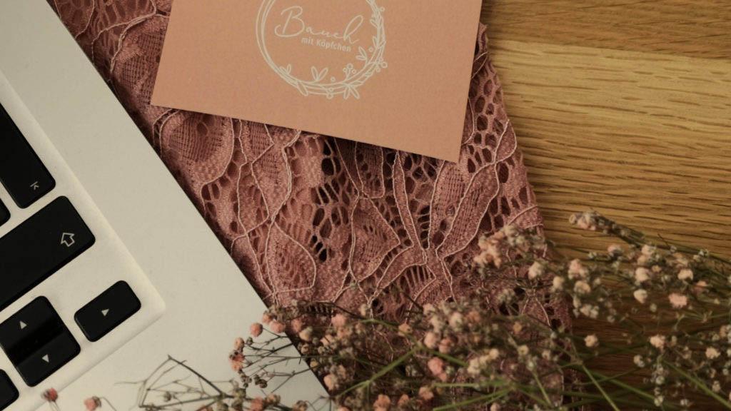 Laptop mit Trockenblumen und Visitenkarte